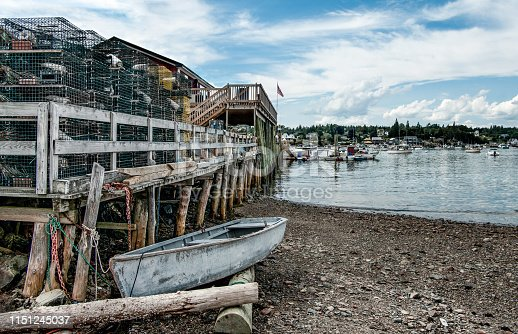 A small boat waits beside a rough wooden pier piled high with lobster traps on a bay in southeast Maine.