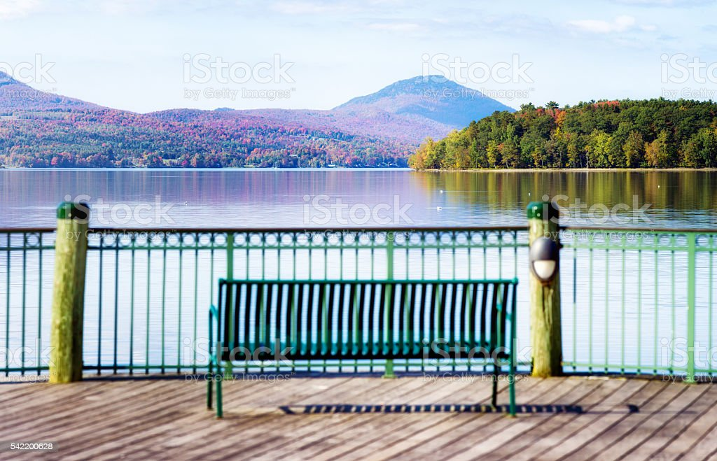 New England lake at Autumn with bench in front panorama stock photo