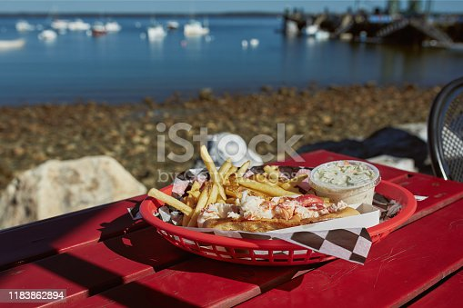 Eating traditional Maine lobster roll with coleslaw and French fries on a waterfront harbor in Lincolnville, Maine.