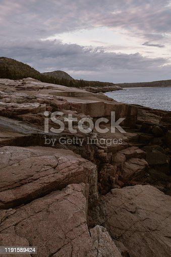 Sunset over rugged coastline of Sand Beach on a cool Fall evening in Acadia National Park on Mount Desert Island, Maine.