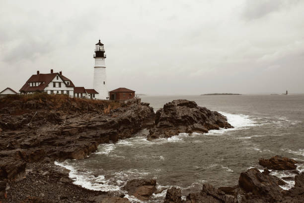 New England road trip in the Fall, USA Portland Head Lighthouse on a cold and stormy Fall day in Cape Elizabeth, Maine, USA. rocky coastline stock pictures, royalty-free photos & images