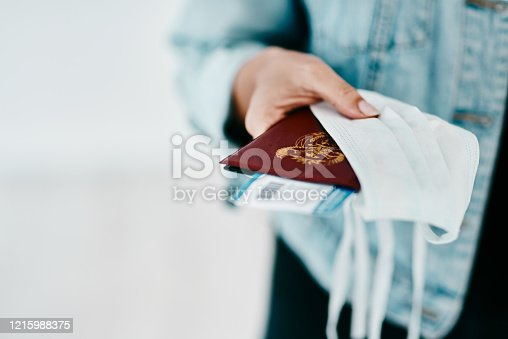 Cropped shot of a woman holding her passport, mask and boarding pass in an airport