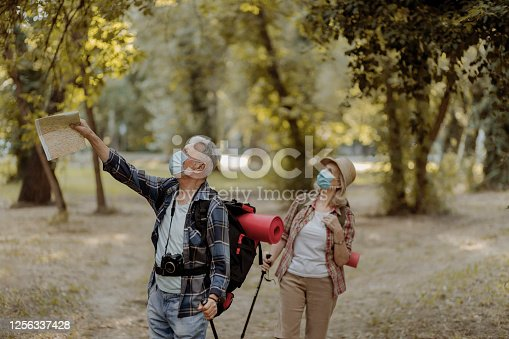 Senior Tourist Couple Travellers Hiking in Nature, Walking and Talking While Wearing Face Protective Masks During Coronavirus Outbreak. Hiking Adventure Travel People Living Active Healthy Lifestyle on COVID 19 Period