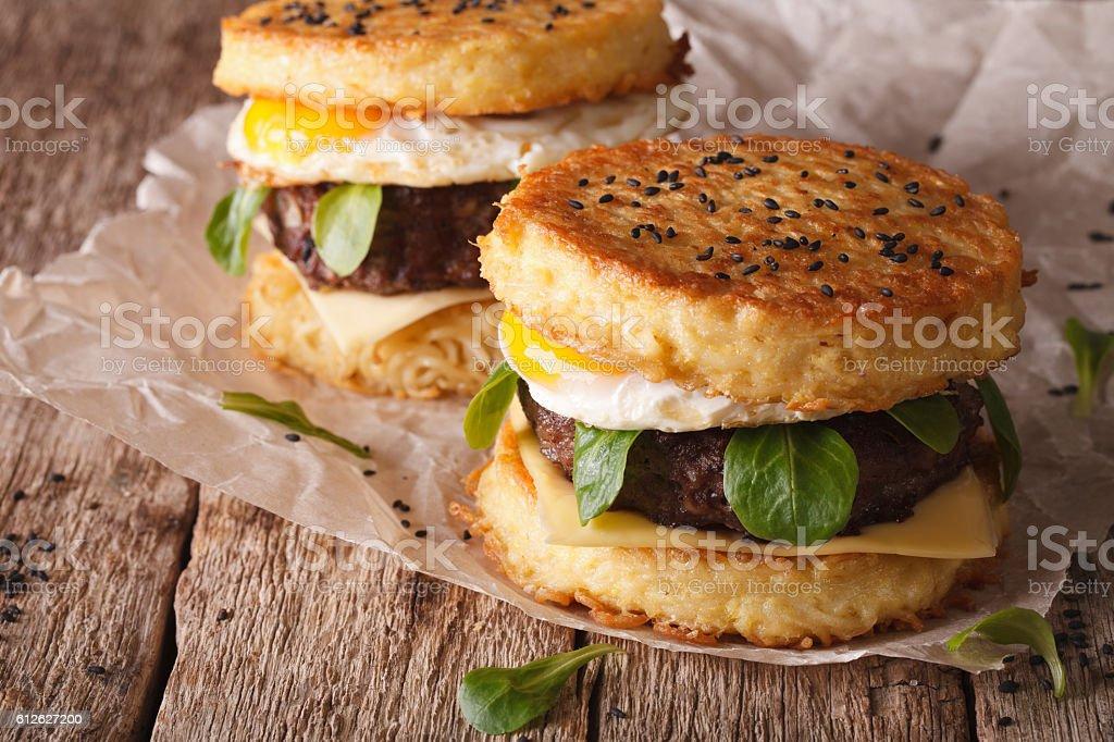 New fast food: ramen burger close-up on the wooden table stock photo