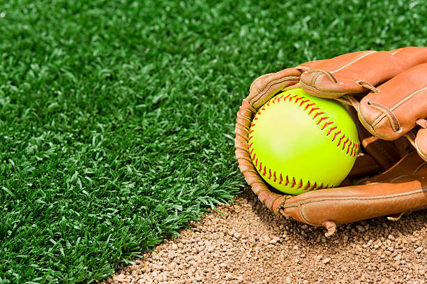 new fast pitch softball in glove sitting on infield - softball stock photos and pictures