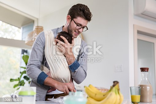 New dad prepares lunch while holding his newborn baby in a baby sling.