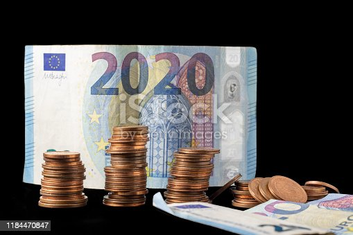 467271788 istock photo New fiscal year 2020 represented with euro bills and coin stacks isolated on black. Conceptual image regarding the economical situation. 1184470847