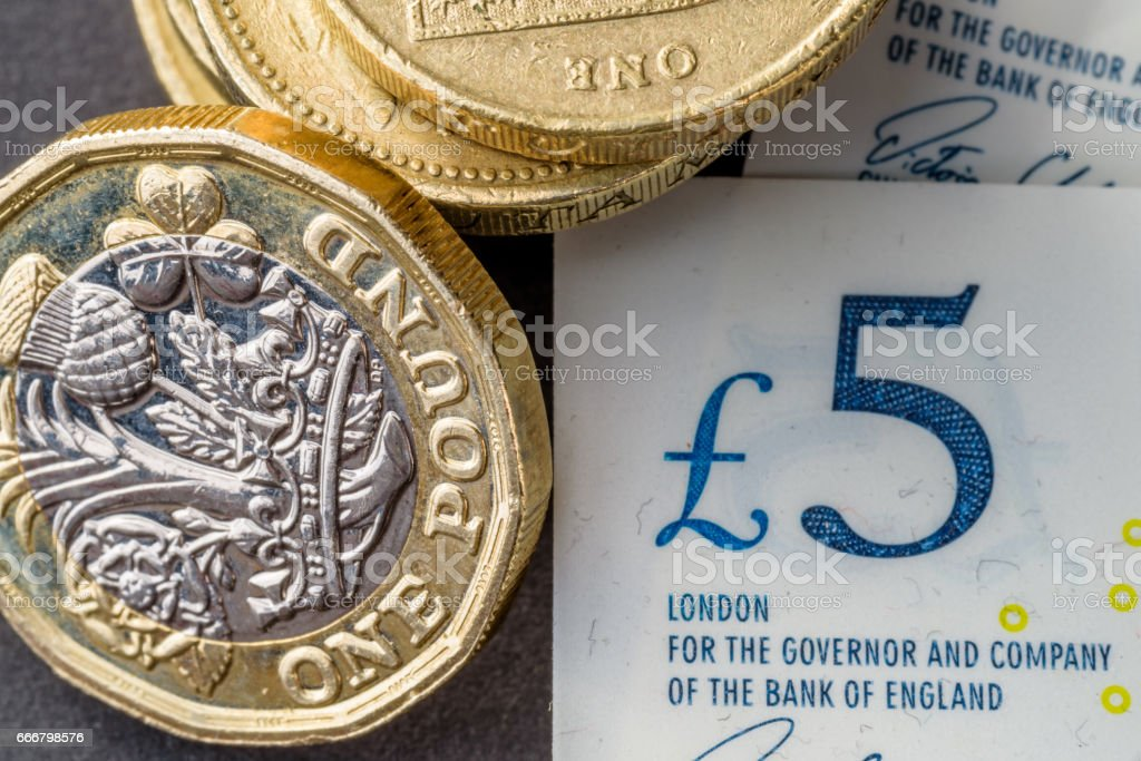 New five sterling pounds note and one pound coin stock photo