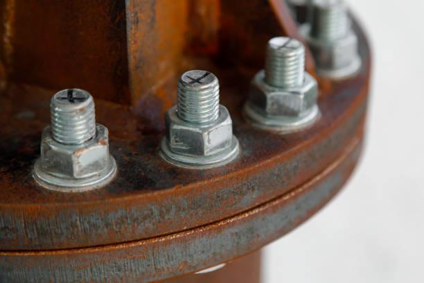 Neue verzinkte Schrauben verbinden alte rostige Metallteile nah auf einem leicht verschwommenen Hintergrund. Das Symbol der Vereinigung der Großen durch die vielen Kleinen – Foto