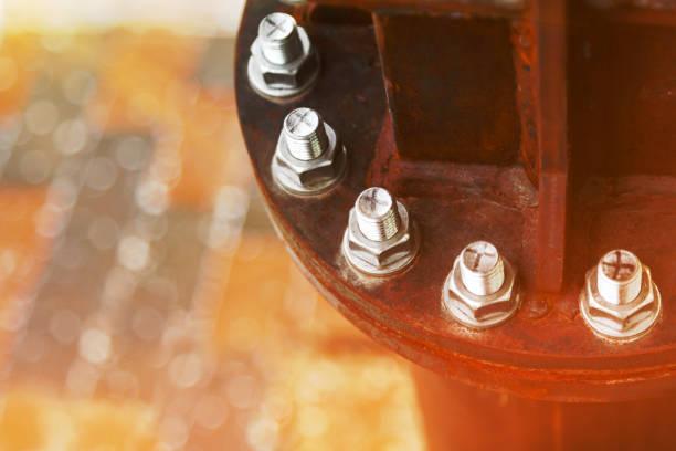 Neue verzinkte Schrauben verbinden alte rostige Metallteile nah auf einem verschwommenen Fliesenhintergrund. Das Symbol der Vereinigung der großen durch die vielen Kleinen. – Foto