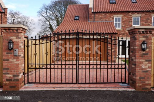 New garage and driveway behind an iron gate in a UK housing development.