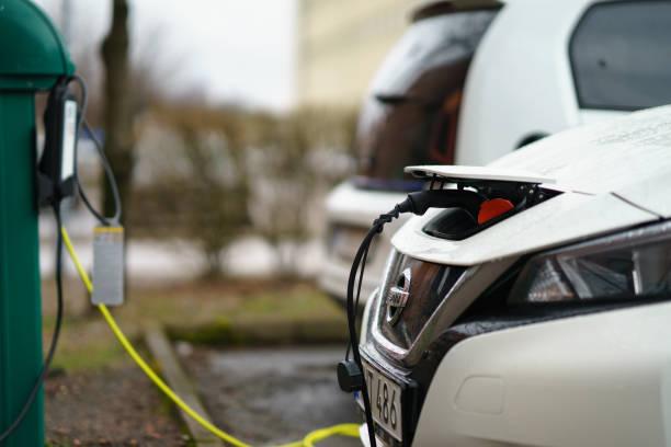 ny generation av nissan leaf laddas på parkeringen av industri område - elbilar laddning sverige bildbanksfoton och bilder
