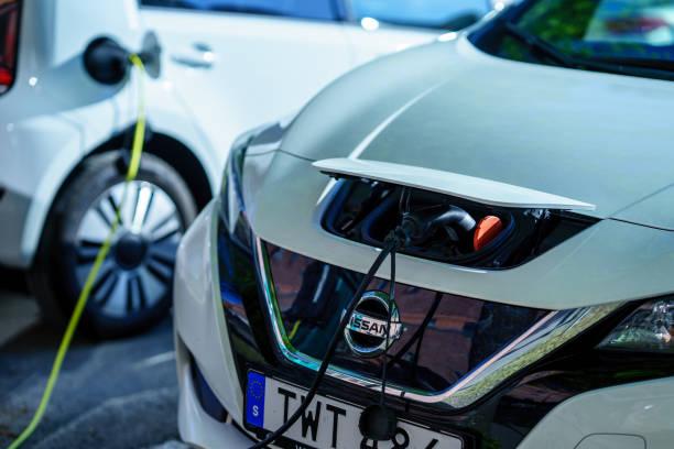 ny generation av nissan leaf laddar på parkeringsplatsen i industriområdet - elbilar laddning sverige bildbanksfoton och bilder