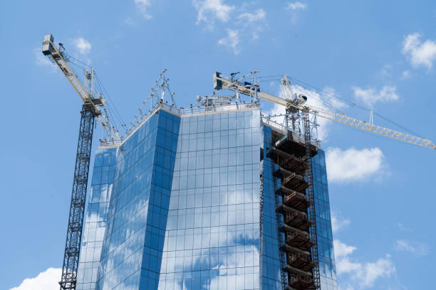 New Glass Building Construction with Cranes on Top Close Up stock photo
