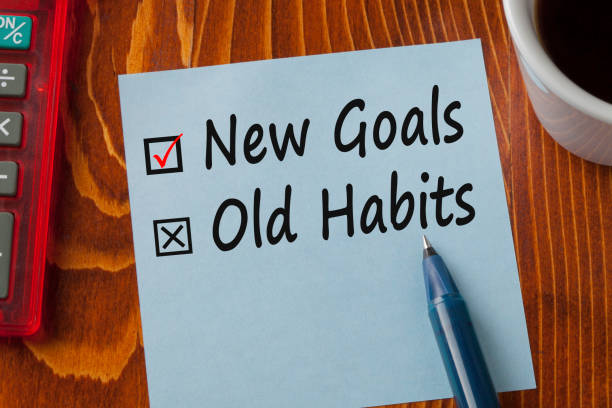 New Goals Old Habits Concept New Goals Old Habits written in note with pen, calculator and cup of coffee on wooden desk. Business concept. Top view. dependency stock pictures, royalty-free photos & images