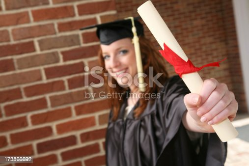 istock New Graduate Holding Diploma, with copy space 173866692