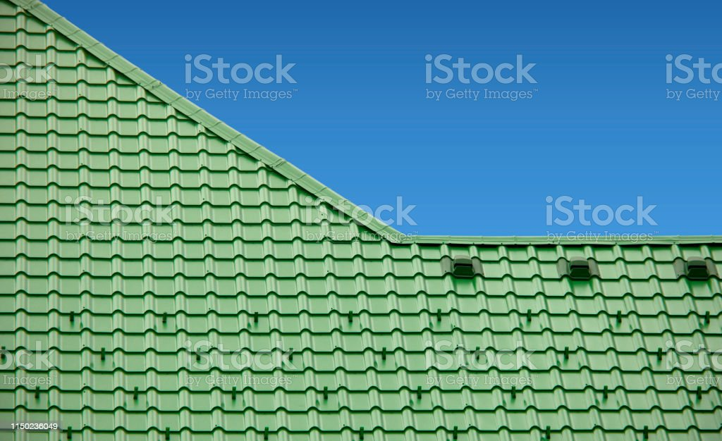 new roof with green sheet metal and background of blue sky