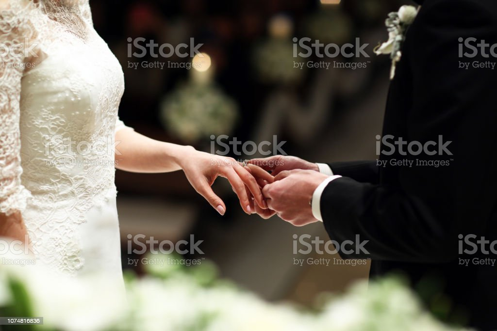 A new groom puts the wedding ring on the bride in wedding ceremony stock photo