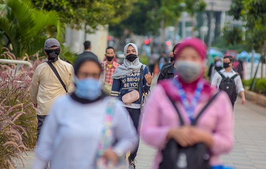 Indonesia, Jakarta - May  12, 2020: Office workers walking at sudirman street with face mask to prevent the transmission of coronavirus