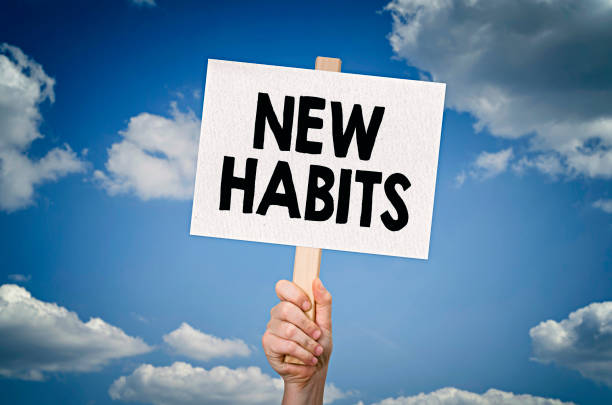 New habits New habits message on board in hand with sky background dependency stock pictures, royalty-free photos & images