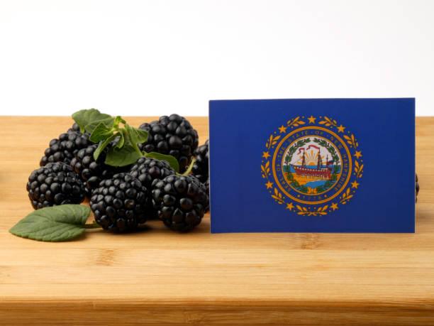 Bandeira de Nova Hampshire em um painel de madeira com amoras isolado em um fundo branco - foto de acervo