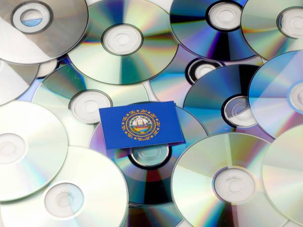 Bandeira de Nova Hampshire, no topo da pilha de CD e DVD isolada no branco - foto de acervo