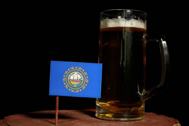 Bandeira de Nova Hampshire com caneca de cerveja isolada no fundo preto - foto de acervo