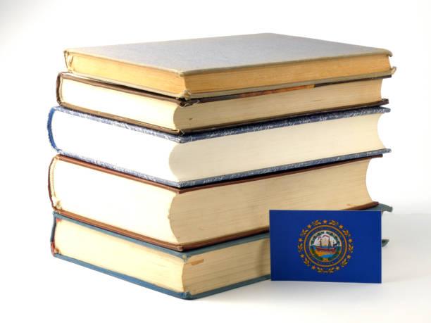 Bandeira de Nova Hampshire com pilha de livros isolado no fundo branco - foto de acervo