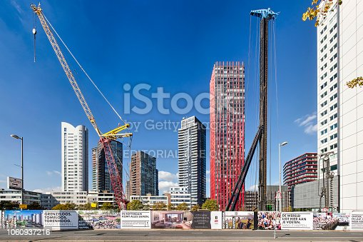 Rotterdam, The Netherlands, September 30, 2018: fenced off building site at Boompjes with a crane and a pile-driver and the highrise of Wijnhaveneiland in the background