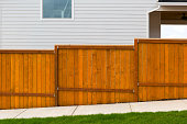 New home backyard red stained cedar wood fence construction in subdivision residential home