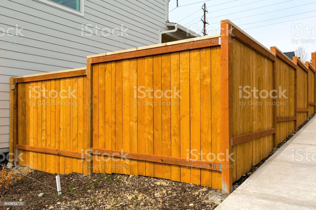 New home backyard wood fence construction in suburban neighborhood