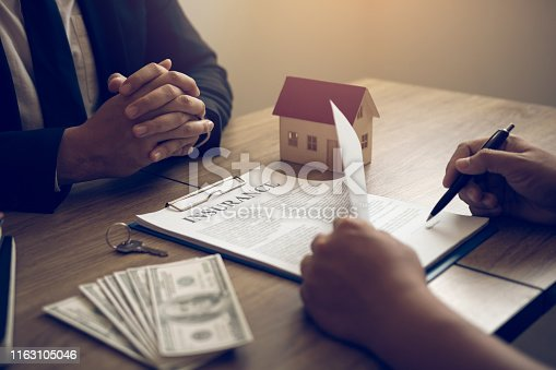 481337750istockphoto New home buyers are signing a home purchase contract at the agent's desk. 1163105046