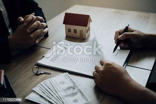 481337750istockphoto New home buyers are signing a home purchase contract at the agent's desk. 1170022898