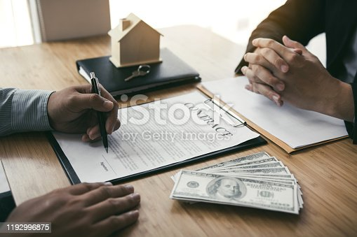 481337750 istock photo New home buyers are signing a home purchase contract at the agent's desk. 1192996875