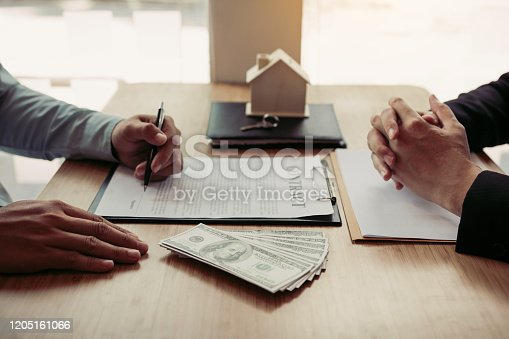 481337750 istock photo New home buyers are signing a home purchase contract at the agent's desk. 1205161066