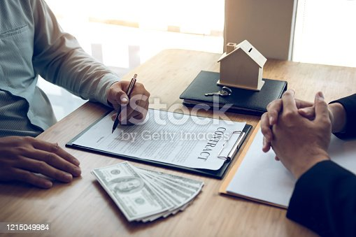 481337750 istock photo New home buyers are signing a home purchase contract at the agent's desk. 1215049984