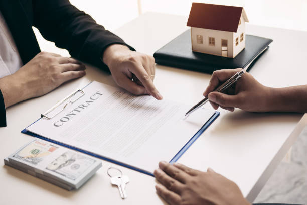 New home buyers are signing a home purchase contract at the agent's desk. New home buyers are signing a home purchase contract at the agent's desk. investor stock pictures, royalty-free photos & images