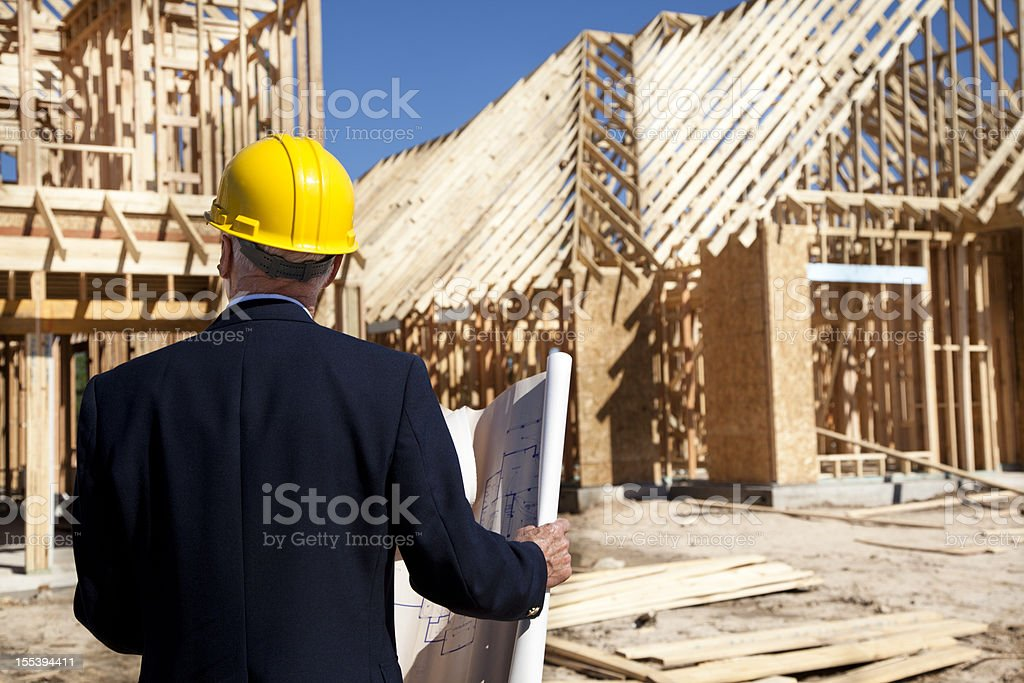 New home construction site with contractor in foreground. Framed buildings. stock photo