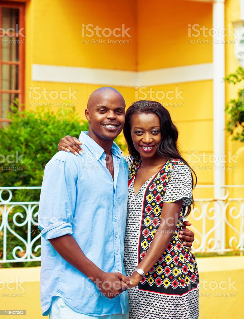 New home Happy african couple embracing in front of their new house. Adult Stock Photo