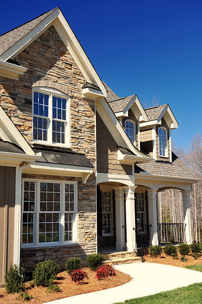 New Home New home with stone facade on clear blue day. stone house stock pictures, royalty-free photos & images