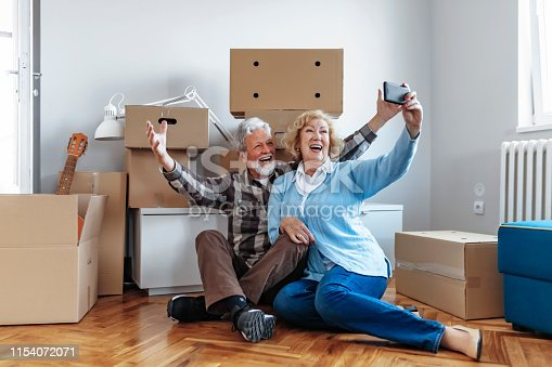 Happy Senior Couple Smiling and Taking a Selfie With a Smartphone in the New Home on Moving Day With Cardboard Boxes in the Background.