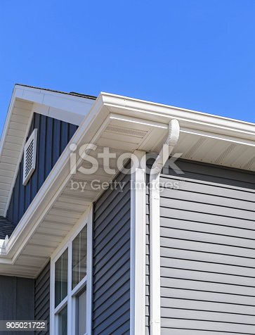 New home with white gutters, soffit and grey vinyl siding. Blue sky is in the background