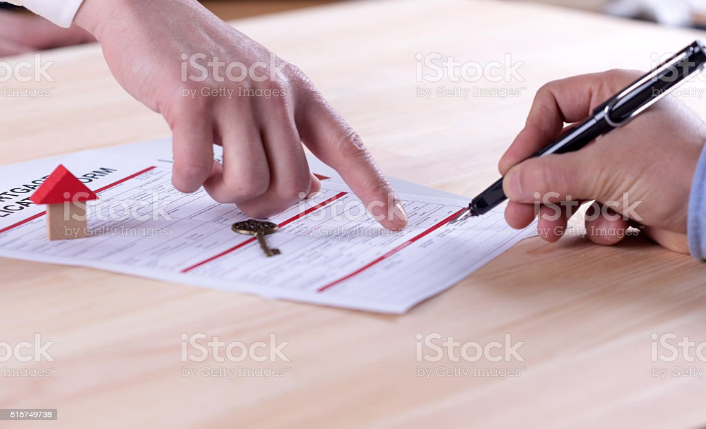 New homeowner signing contract of house sale or mortgage papers stock photo