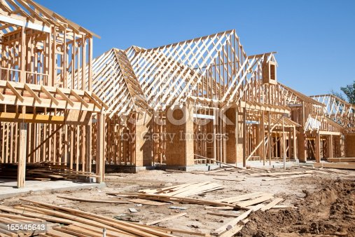 istock New homes construction site. Framed houses. Lumber. Building. 155445643