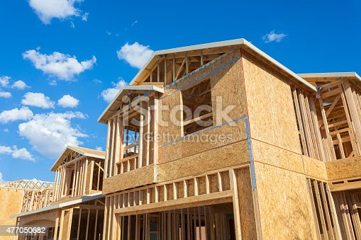 A new house being built in the suburbs of Las Vegas. Here you can see the wooded frame taking the shape of the final house. Photographed with a blue sky in the background.
