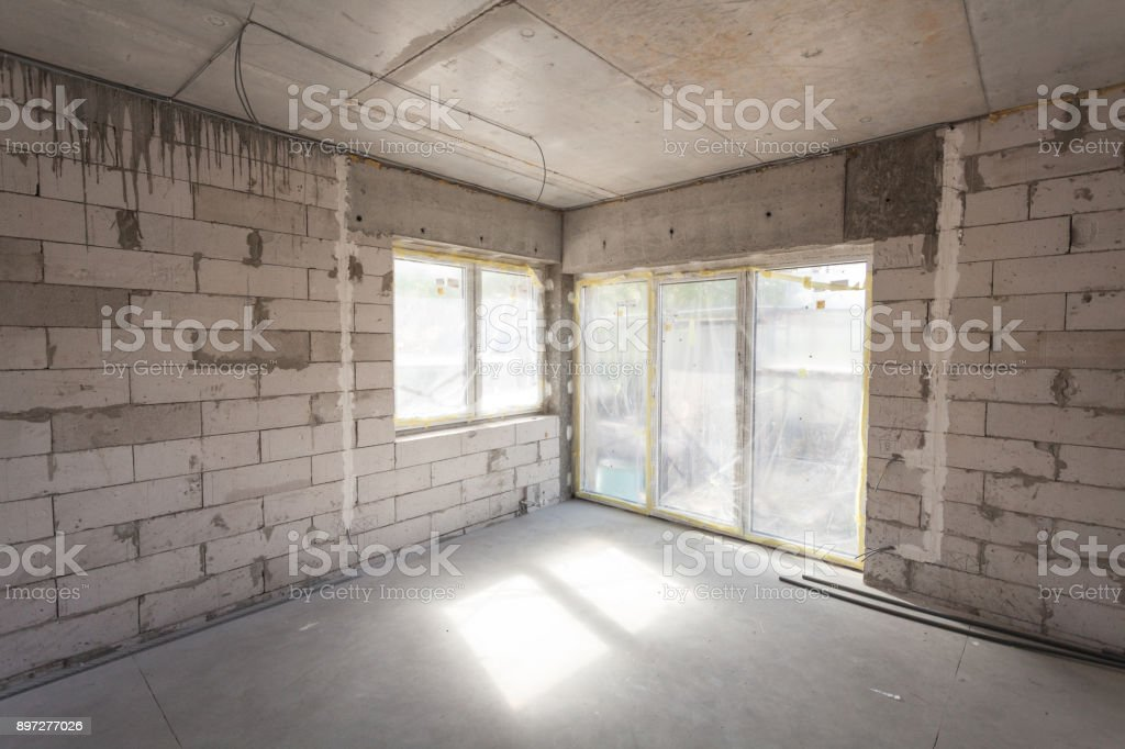 New house under construction. Aerated concrete blocks, cement brickwork walls, plastic window, electric wiring installation. Cement covering in empty room stock photo