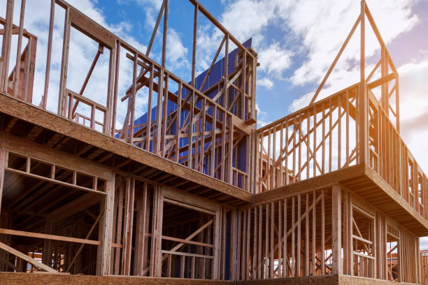 New house under construction framing against a blue sky New house under construction framing beam against a blue sky construction industry stock pictures, royalty-free photos & images