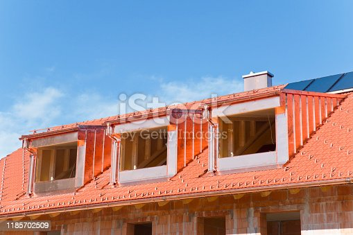 New house under construction with copper paneling of dormers