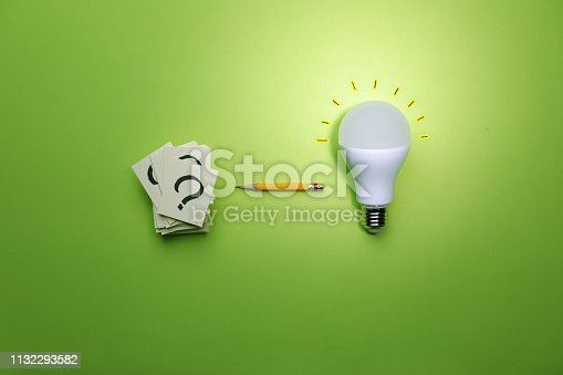 Light bulb and question mark stack on green background