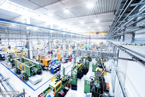 Horizontal high angle view color image of futuristic factory. Industrial aisle surrounded by modern machines which having busy robotic arms with molding shapes and producing plastic pieces for variety of industry. Labor intensive production line with manufacturing equipment - boxes, crates, crane, packages, pallets, space for copy
